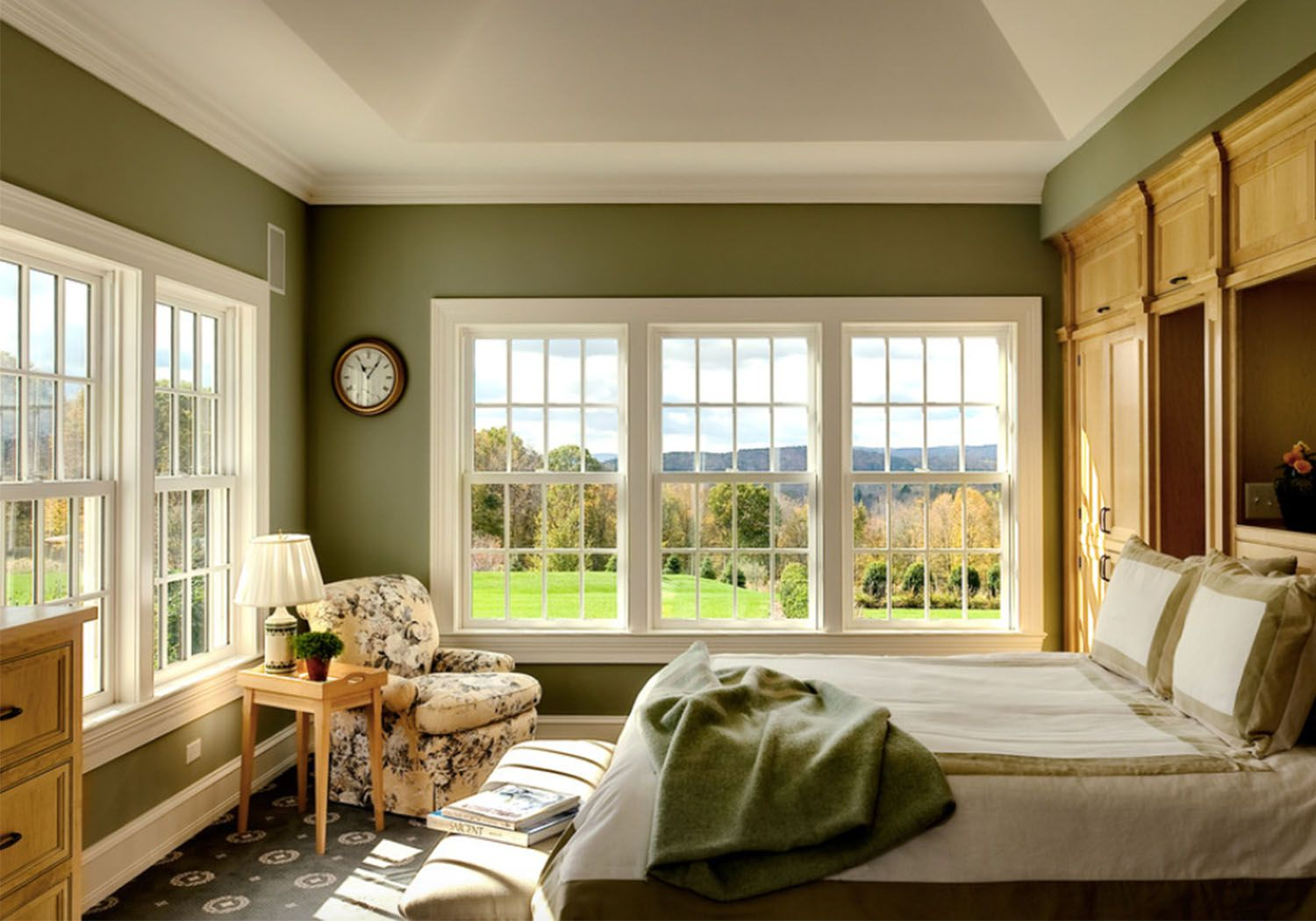 Soft Olive Green Walls Complement The Wooden Furnishings Floral Print Armchair And Green Green Master Bedroom Green Bedroom Colors Traditional Bedroom Design