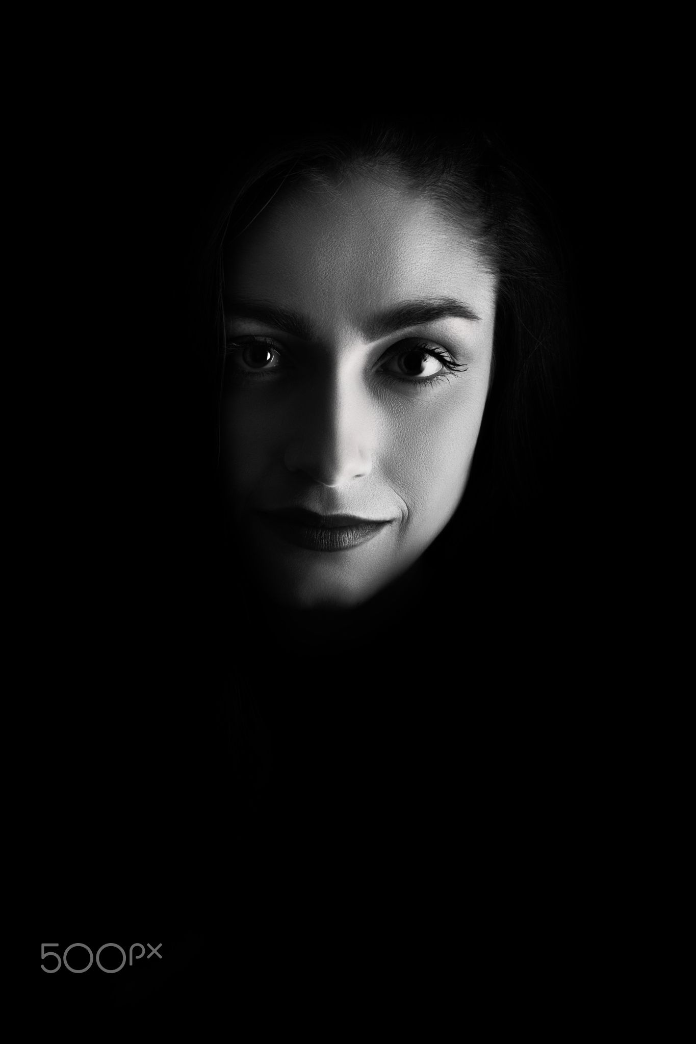 smiling woman face - smiling woman face on black background with copyspace, monochrome