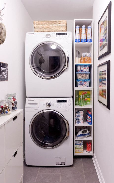 Compact Laundry Room With Stackable Front Load Washer And Dryer Next To Freestanding Shelving Over