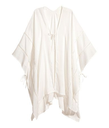 d9bace9ec Natural white. Poncho in airy, woven viscose fabric with lace insert  details. Ties
