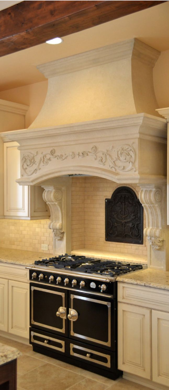 A cooker hood supported by a pair of ornate decorative corbels. You can find similar range hood corbels and wood appliques at www.buycarvings.com