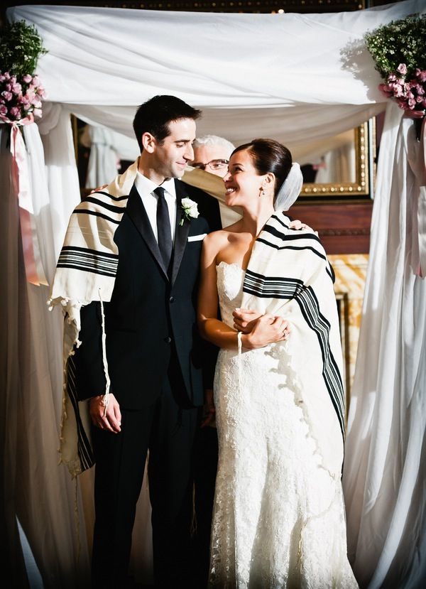 A Traditional Jewish Wedding Ceremony With The Bride And Groom Beaming