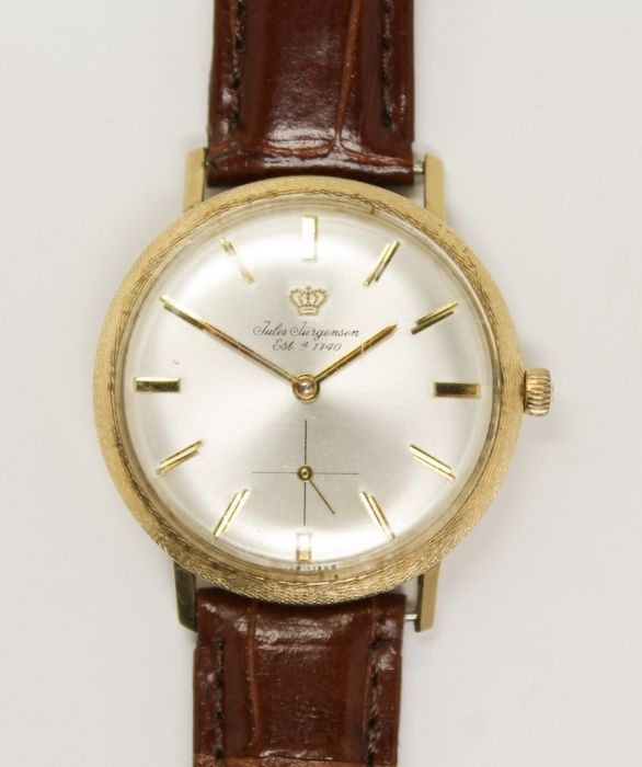 This is a handsome vintage men's dress wristwatch from Jules Jurgensen dating to the 1950s/60s. Rendered in fine 14k yellow gold, the case frames a large, silver tone dial.