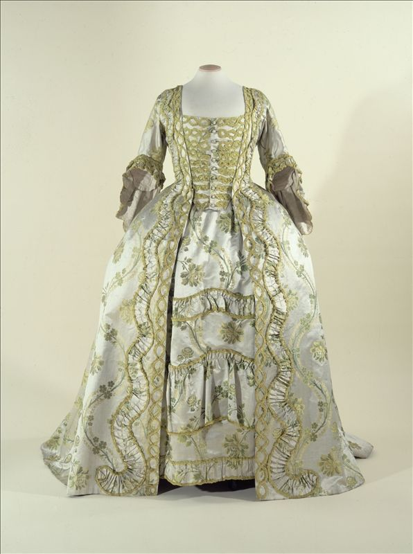"Robe à la Française ""Sack-back gown"", c.1750-1760, France, Dress: liseré satin, grey and green silk. Lining: striped taffeta, green and violet silk. Green silk chenille appliqués. ""This robe à la française is a copybook illustration of the Rococo aesthetic, which saw beauty as necessarily dynamic: the undulation of the flowers on the fabric and the silk chenille appliqués on the bodice were harmoniously matched by the swaying of the panniers as the wearer moved about."""