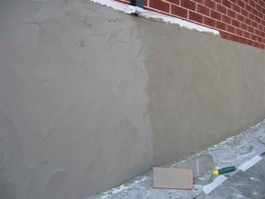 Parging applying a mortar coat with a trowel to control for Block wall foundation