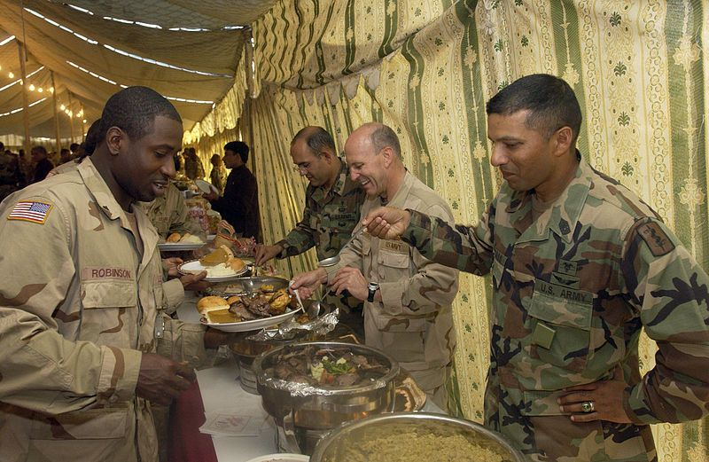 U.S. Navy Rear Adm. Mike Lefever, center, serves Thanksgiving Dinner along side 212th Mobile Army Surgical Hospital (MASH) Commander Col. Lugo and Command Sgt. Maj. Ramdass
