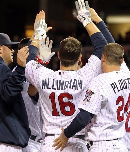 Minnesota Twins' Josh Willingham is congratulated by teammates after hitting a three-run home run against Oakland Athletics pitcher Brian Fuentes during the ninth inning to win the baseball game 3-2, Tuesday, May 29, 2012, in Minneapolis