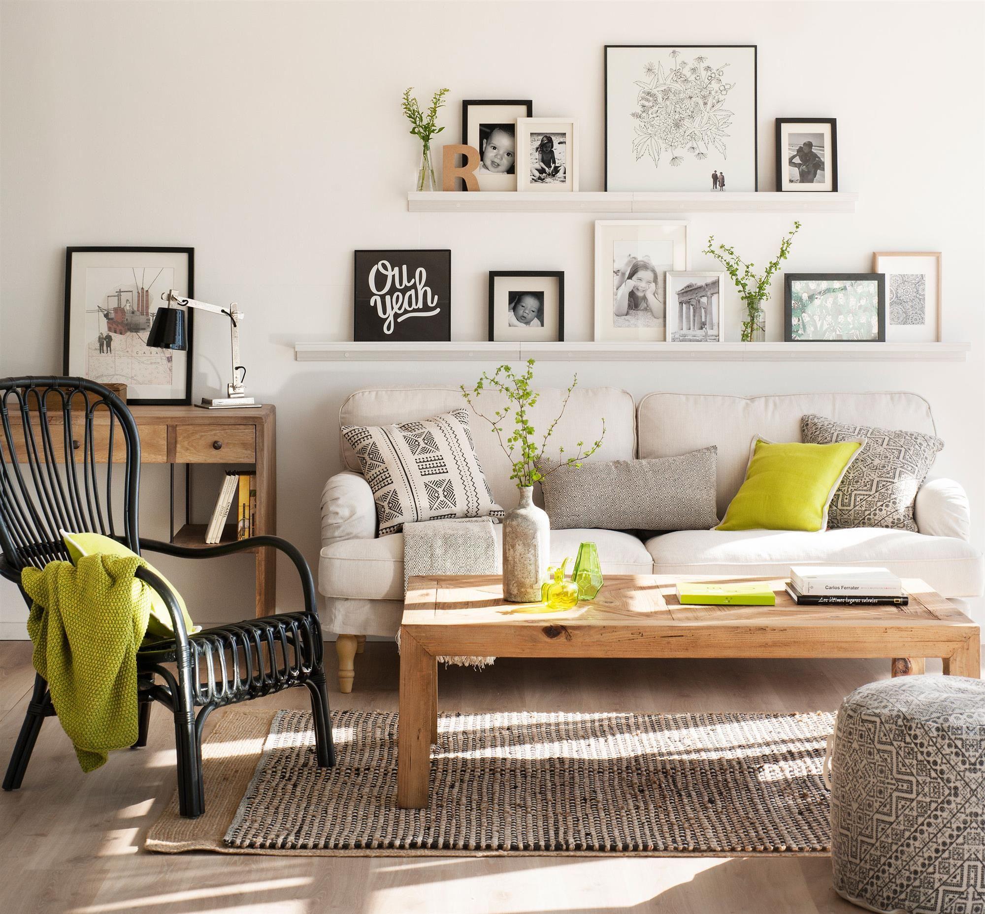 Salón con pared de cuadros sobre estantería fina, sofá gris y mesa ...