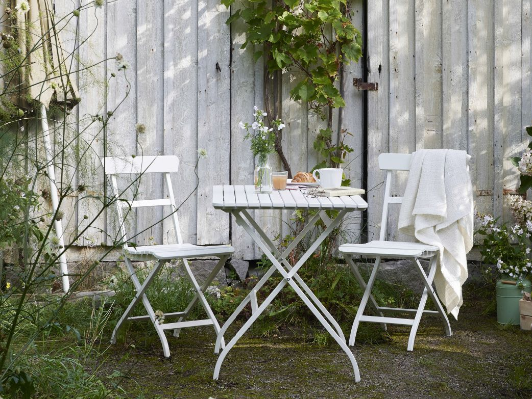 A garden with a white small foldable table and two chairs, all in ...
