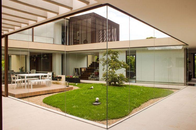 jardin intérieur entouré de baies vitrées avec terrasse, coin-repas ...