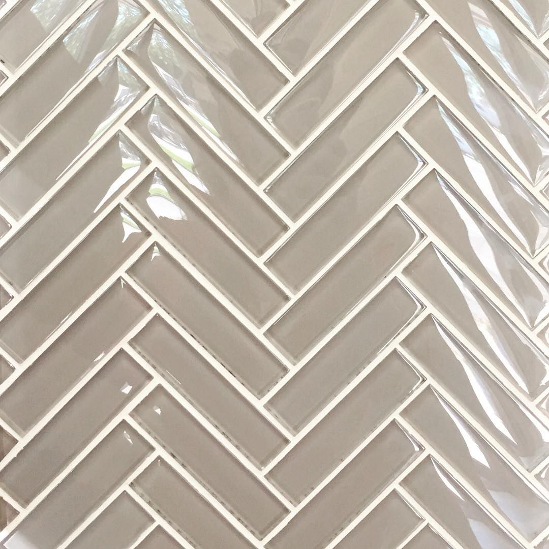 Here classic white grout highlights the herringbone pattern of modern glass tile it also