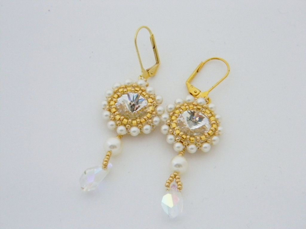 Swarovski crystal rivoli encased in gold colored seed beads and Swarovski cream pearls, finished with cream pearls and clear drops and gold plated lever backs