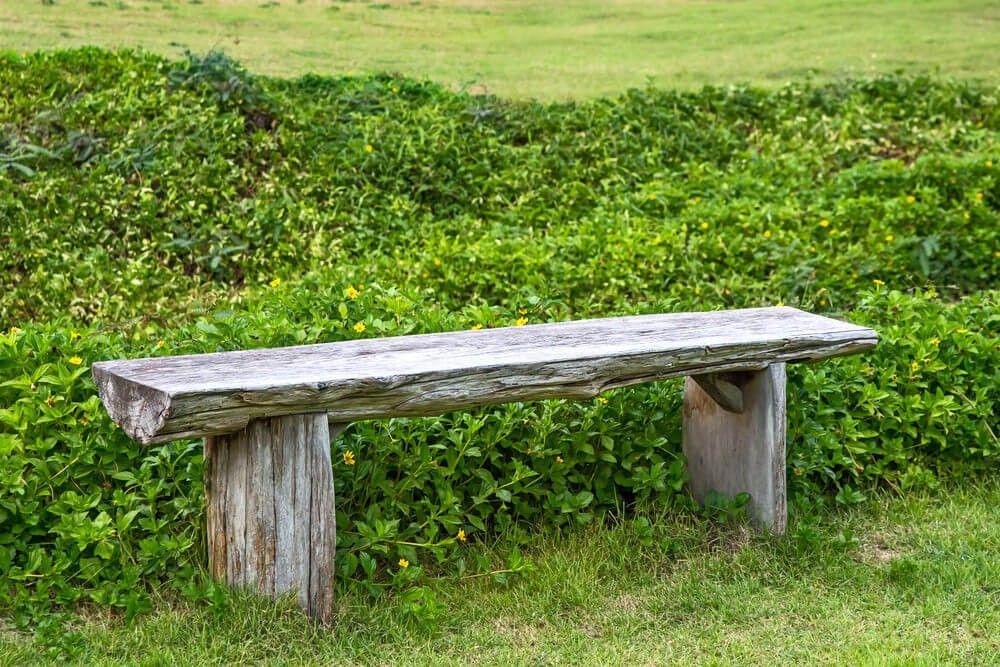 Eine einfache lange Holzbank ohne Arme oder Rückenlehne. Dies ...