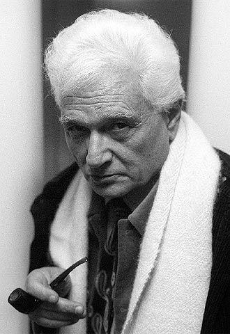 Fotografía de Jacques Derrida luciendo una bella chalina blanca, mirando de frente a la cámara y portando una pipa en su mano derecha.