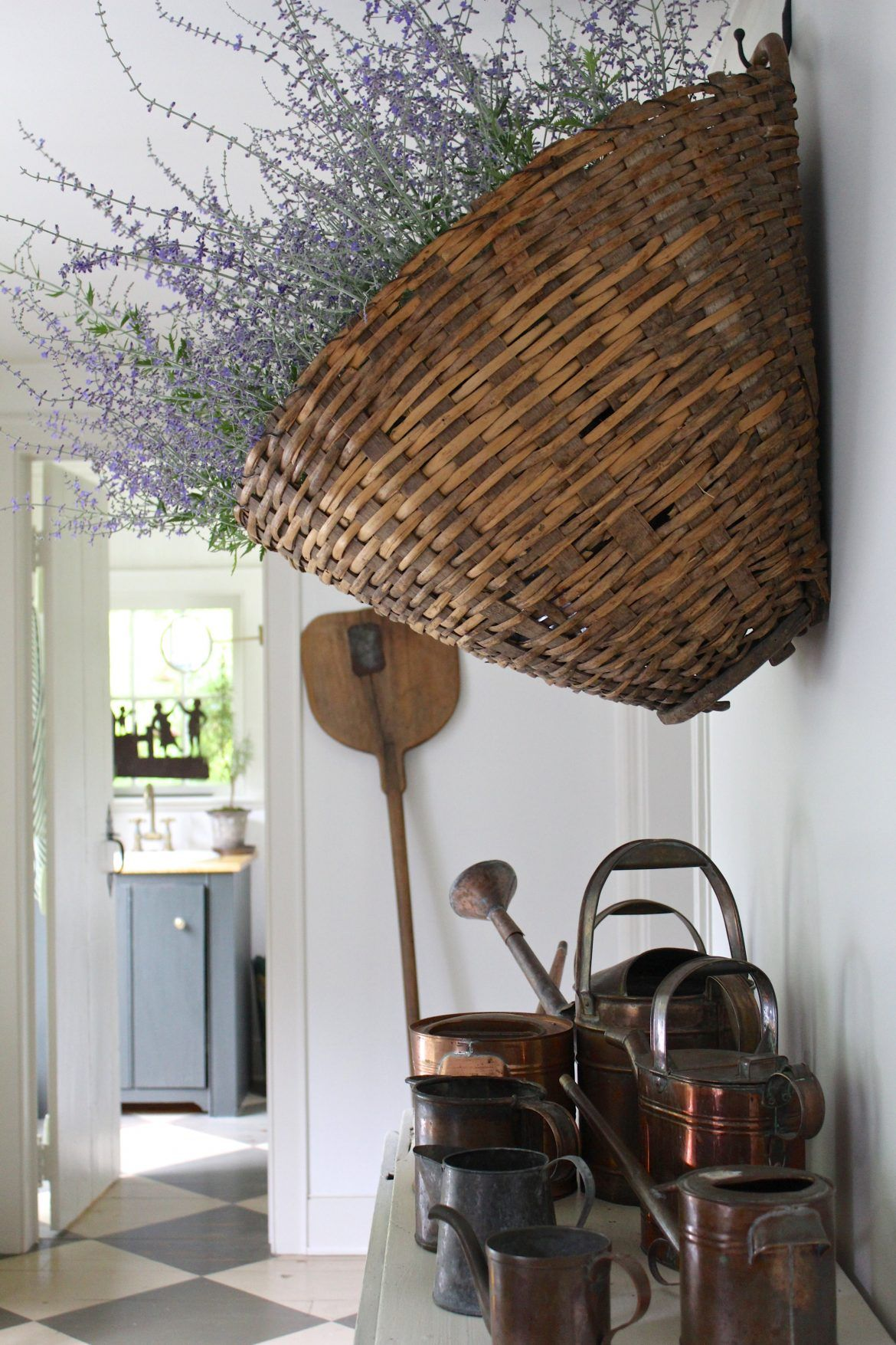 basket full of sage and a collection of watering cans