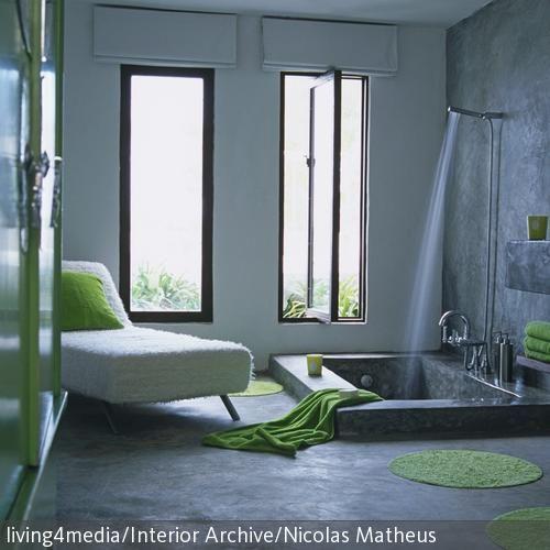 Eingelassene Badewanne wände boden und waschbecken sind aus beton gestaltet die