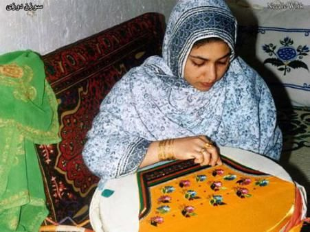A Qeshm woman hand embroidering the traditional snug-fitting shalvar which the women wear.