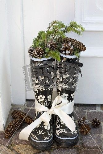 Black and white wellies as Christmas decoration with pinecones, fir tree branch and white ribbon