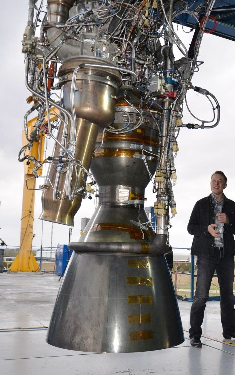 elon musk standing next to the 100th merlin 1d rocket engine produced by spacex 787