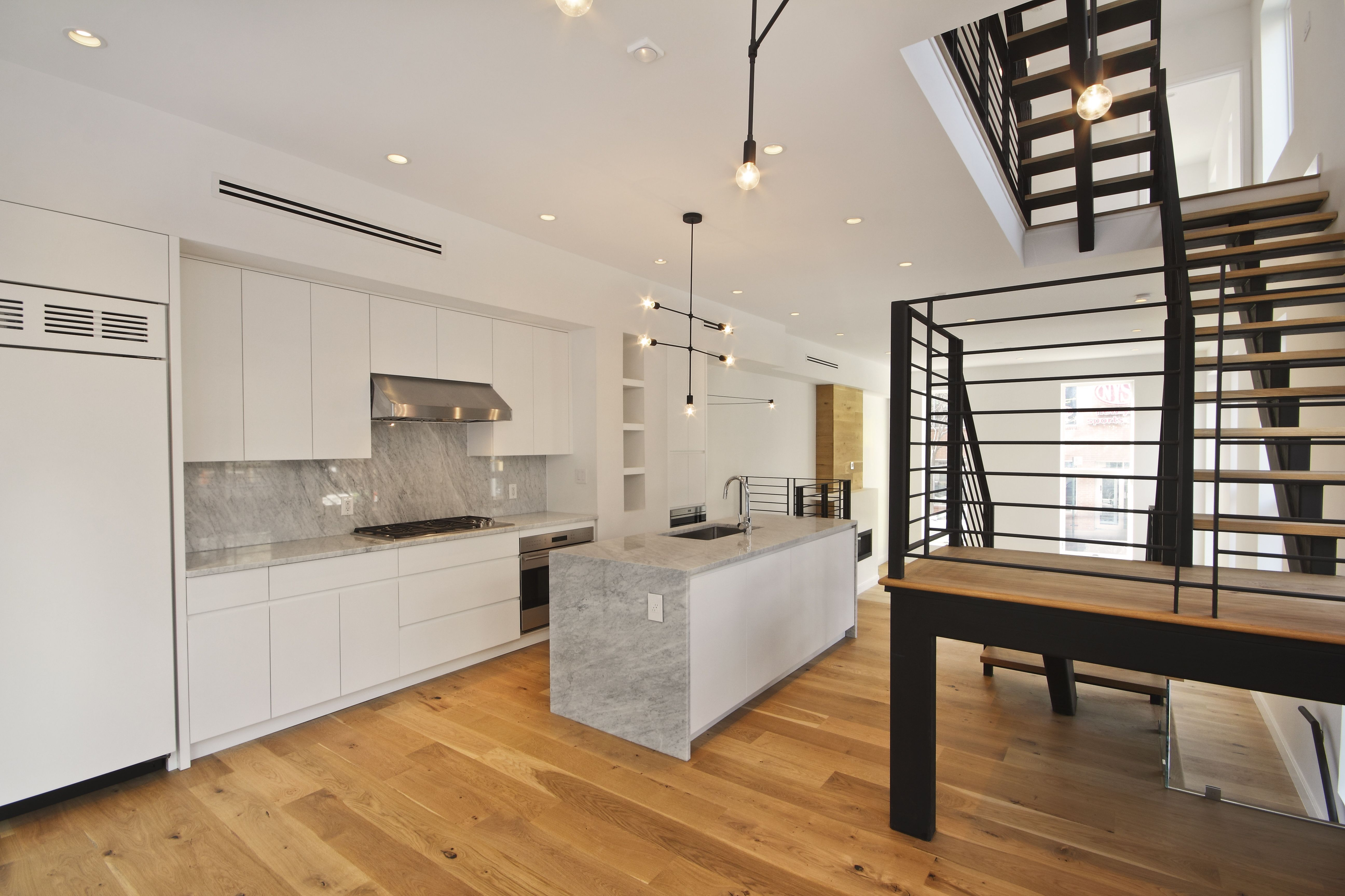 Kitchen With White Cabinets With Finger Pulls Marble Waterfall Island And Custom Matte Black Powder Coate White Kitchen Cabinets White Cabinets Brass Lighting