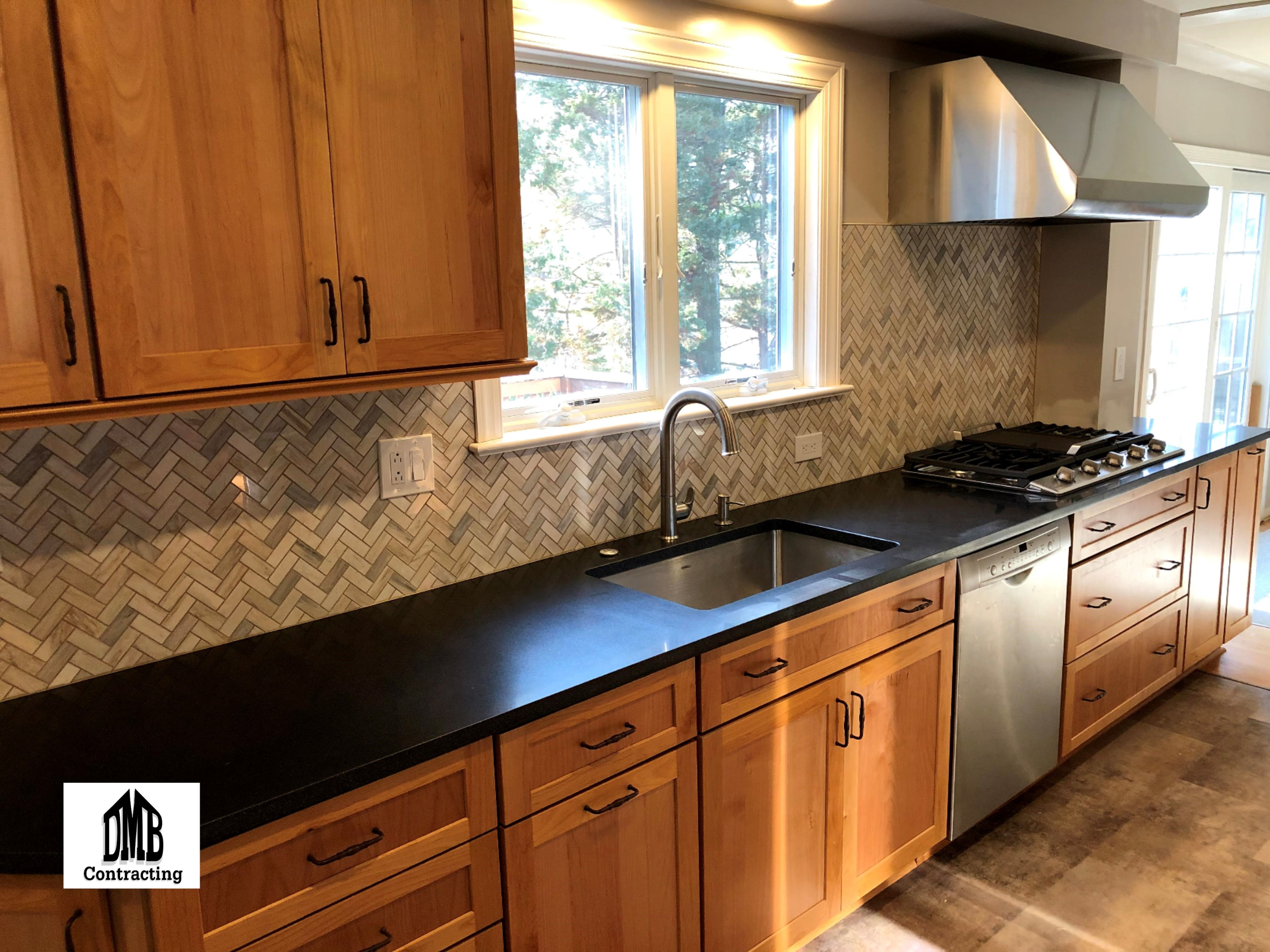 simple black countertops paired with a herringbone pattern backsplash in 2020 black kitchen on kitchen decor black countertop id=83533