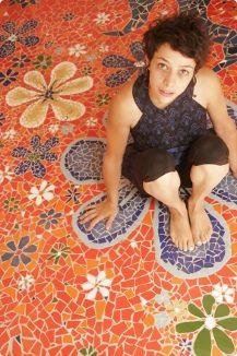 Amandine Serran, assise la mosaïque de fleurs co-réalisée avec Juan-manuel Hernandez