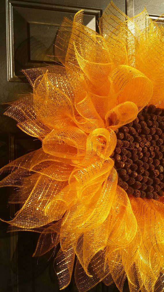 *****US ORDERS*****Brighten your entryway with this cheerful deco mesh sunflower! It is large at 28 diameter. The center is composed of pine cones to give it a realistic look. Its a perfect choice to hang for the summer!  Here are some answers to some Frequently Asked Questions about the Sunflower:  ***I would recommend a covered porch for the sunflower. It is not suitable for direct exposure to the elements  ***It is 28 inches in diameter and very full and fluffy  ***During shipping the…