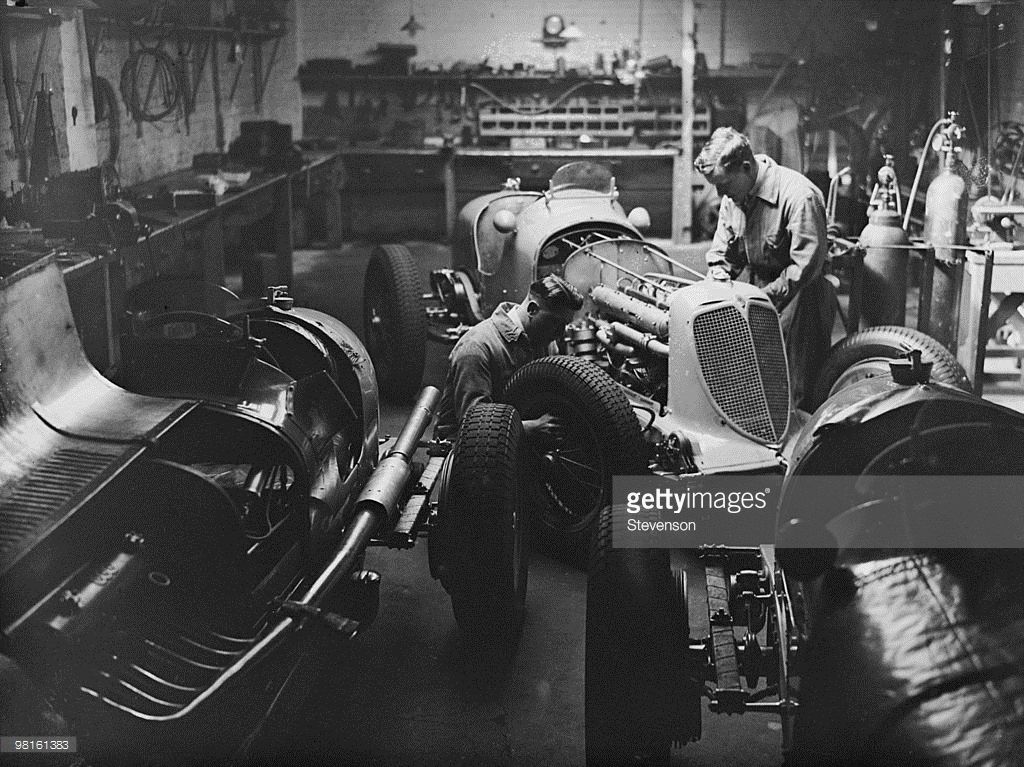 Mechanics at work on B. Bira's racing car in his garage at Ravenscourt Park, London, 31st March 1938. Bira will be driving the car, an ERA (English Racing Automobiles) C-type named 'Hanuman', in the Coronation Trophy Race at Crystal Palace on the 2nd April. B. Bira is the racing name of Prince Birabongse Bhanudej of Siam.