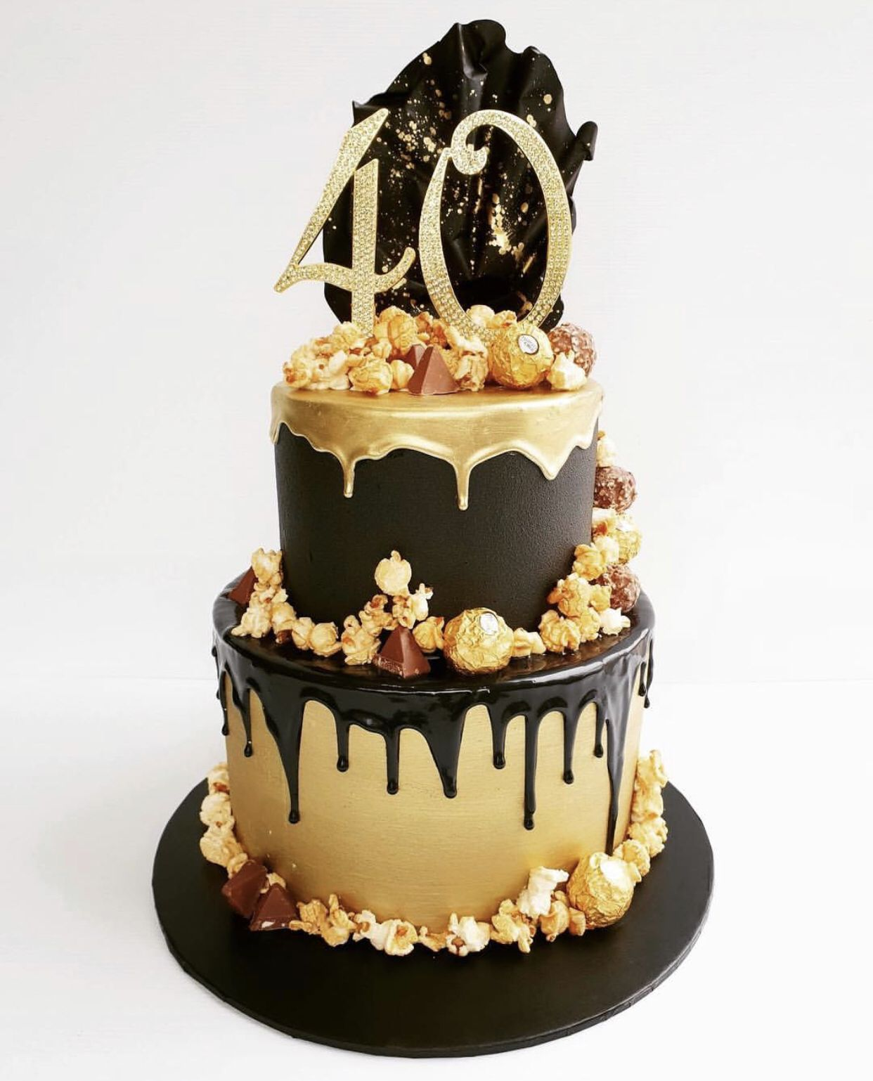 Two Tiers Of Mudcake Decorated In A Stunning Black And Gold Theme