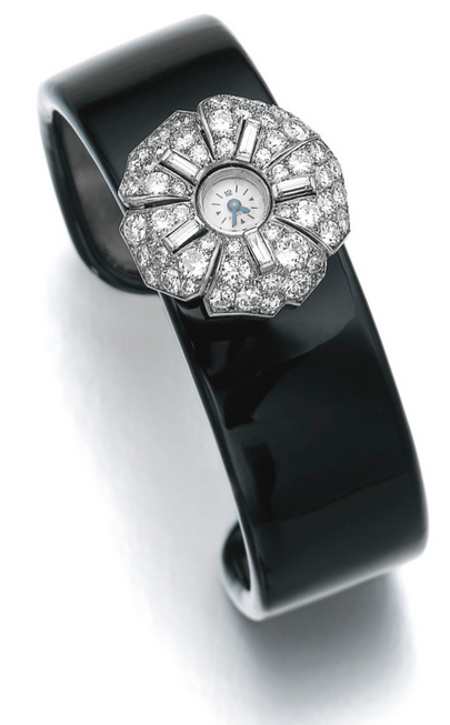 Diamond watch/clip brooch, Cartier, 1930s, on an enamel bangle The watch/brooch of floral design, set with circular-, single-cut and baguette diamonds, manual winding, dial signed Cartier, numbered, French assay marks; with a black enamel bangle mount, inner circumference approximately 158mm.