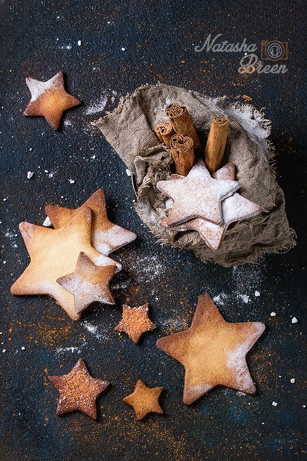 Cookie's Universe. Star Shape Sugar Cookies - Homemade shortbread star shape sugar cookies with sugar and cinnamon powder in old tin can sackcloth rag with cinnamon sticks on dark wooden background. Christmas treats. Overhead view