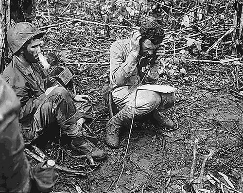 US Marine battalion commanding officer Lieutenant Colonel John Weber receiving a report from a company commander, Cape Gloucester, New Britain, Bismarck Archipelago, Jan 1944.