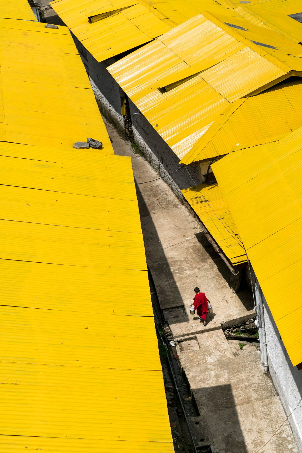 A young monk in red robes runs through a sea of yellow rooftops at Tawang Monastery, the second largest Buddhist monastery in the world. The monastery is located in Tawang, a town in the far northwest reaches of Arunachal Pradesh, a state in Northeast India.