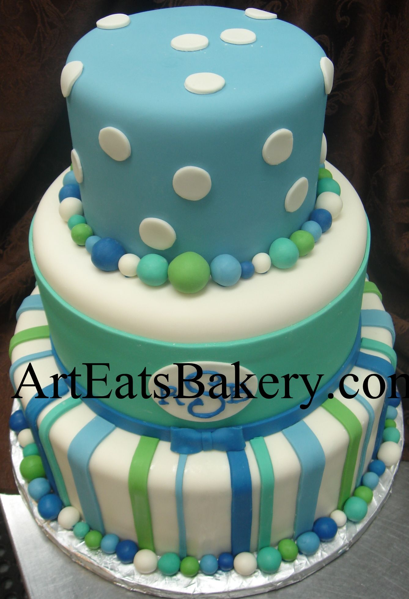 Three tier blue, white and green polka dot and stripe boys baby shower unique fonant cake with monogram and bow  www.arteatsbakery.com