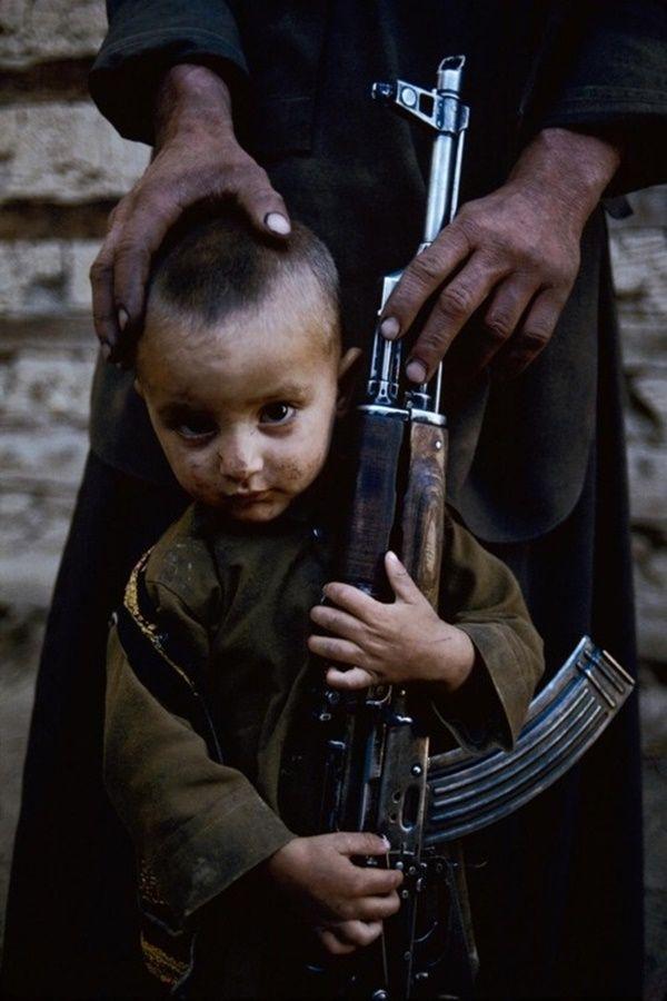 Un joven se coloca al lado de AK-47 de su padre.  Kabul, Afganistán, 1992