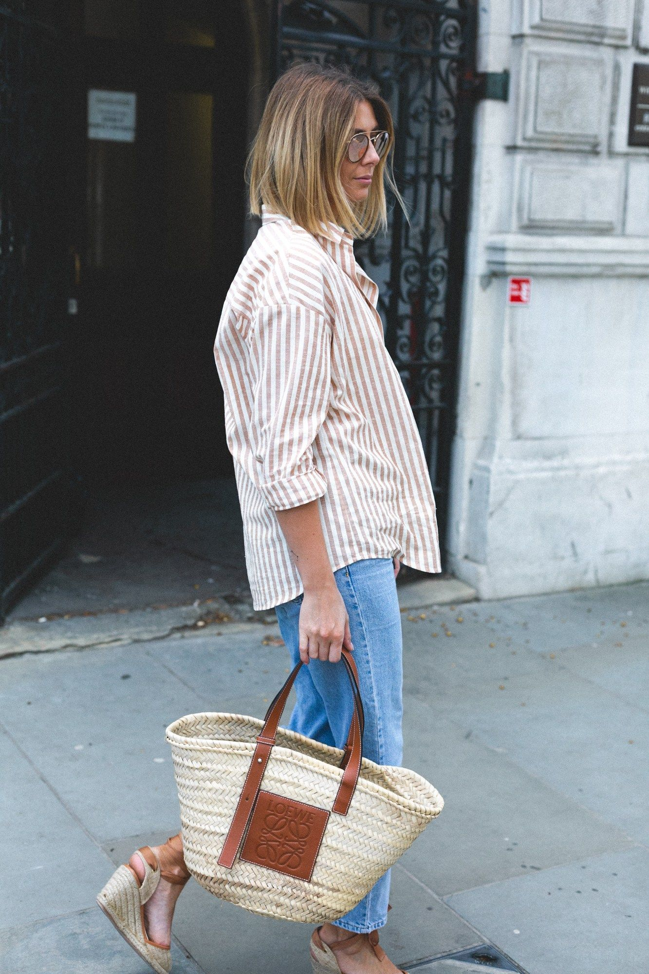 d1937046e9b Emma Hill wears stripe shirt, loewe basket bag, light wash jeans, wedge  espadrilles. spring outfit, casual outfit