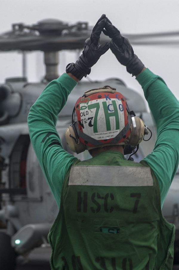 GULF OF OMAN (Aug. 28, 2013) Aviation Electronics Technician Airman Sean Owens directs an MH-60S Sea Hawk helicopter assigned to the Dusty Dogs of Helicopter Sea Combat Squadron (HSC) 7 on the flight deck of the aircraft carrier USS Harry S. Truman (CVN 75).