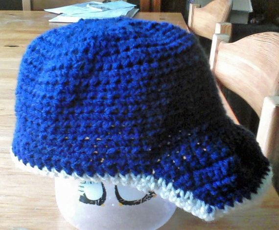"""This is an baby hat made to look like a Baseball Cap! It would be perfect for the little Sluggers in your family to wear while you watch your team duke it out on the Diamond! This will fit approx a size 6 months to 12 months, and it measures approx. 8.5"""" x 5"""". The hat is made with 100% soft Acrylic yarn, and is easy to care for. It is machine washable and dryable."""