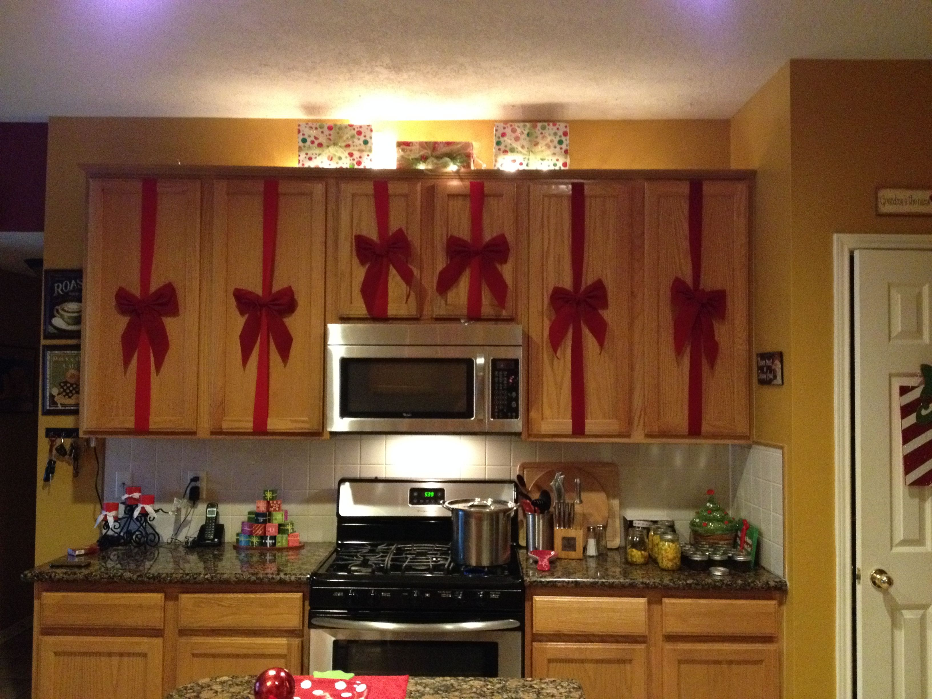Christmas Kitchen Decorating Easy Red Ribbons And Bows On The Cabinet Doors And Some Wrapped Box Holiday Kitchen Decor Christmas Kitchen Cozy Kitchen Decor