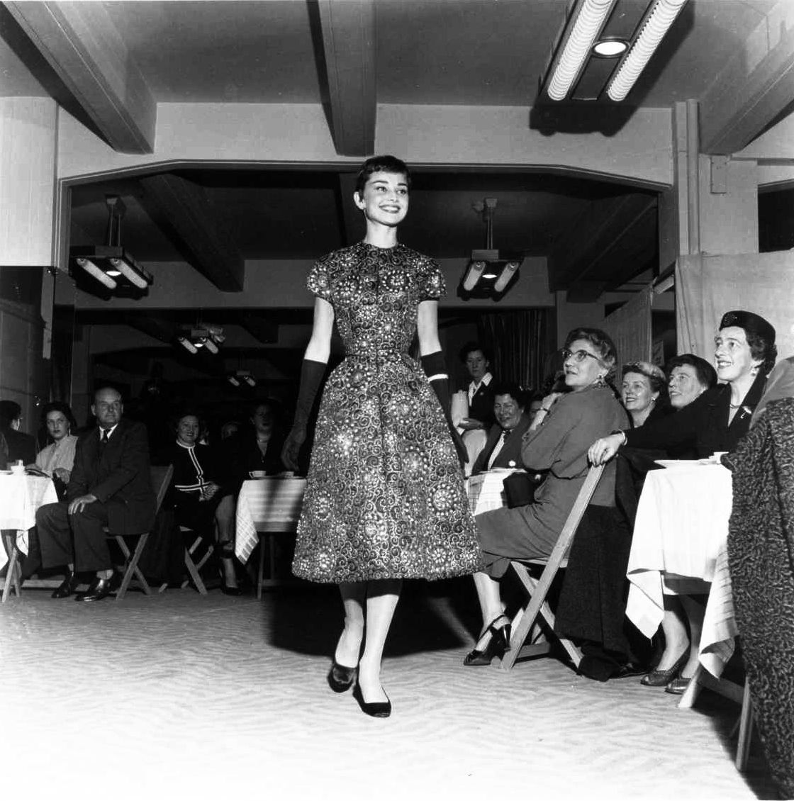 Audrey Hepburn modeling in a charity fashion show at Gerzon Kalverstraat, Amsterdam, November 2, 1954. The fashion show benefited the Joint Military Funds of Shop Gerzon Kalverstraat.