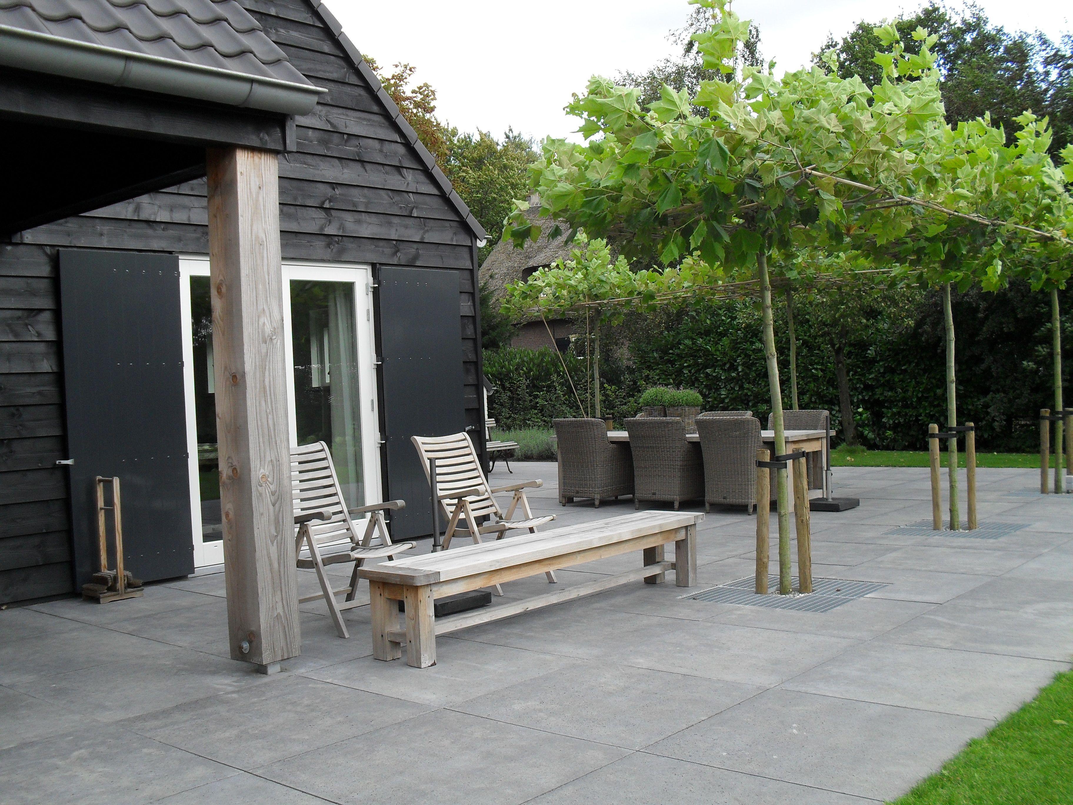 Landelijke tuin met dakplataan en schellevis tegels for Landelijke tuin aanleggen