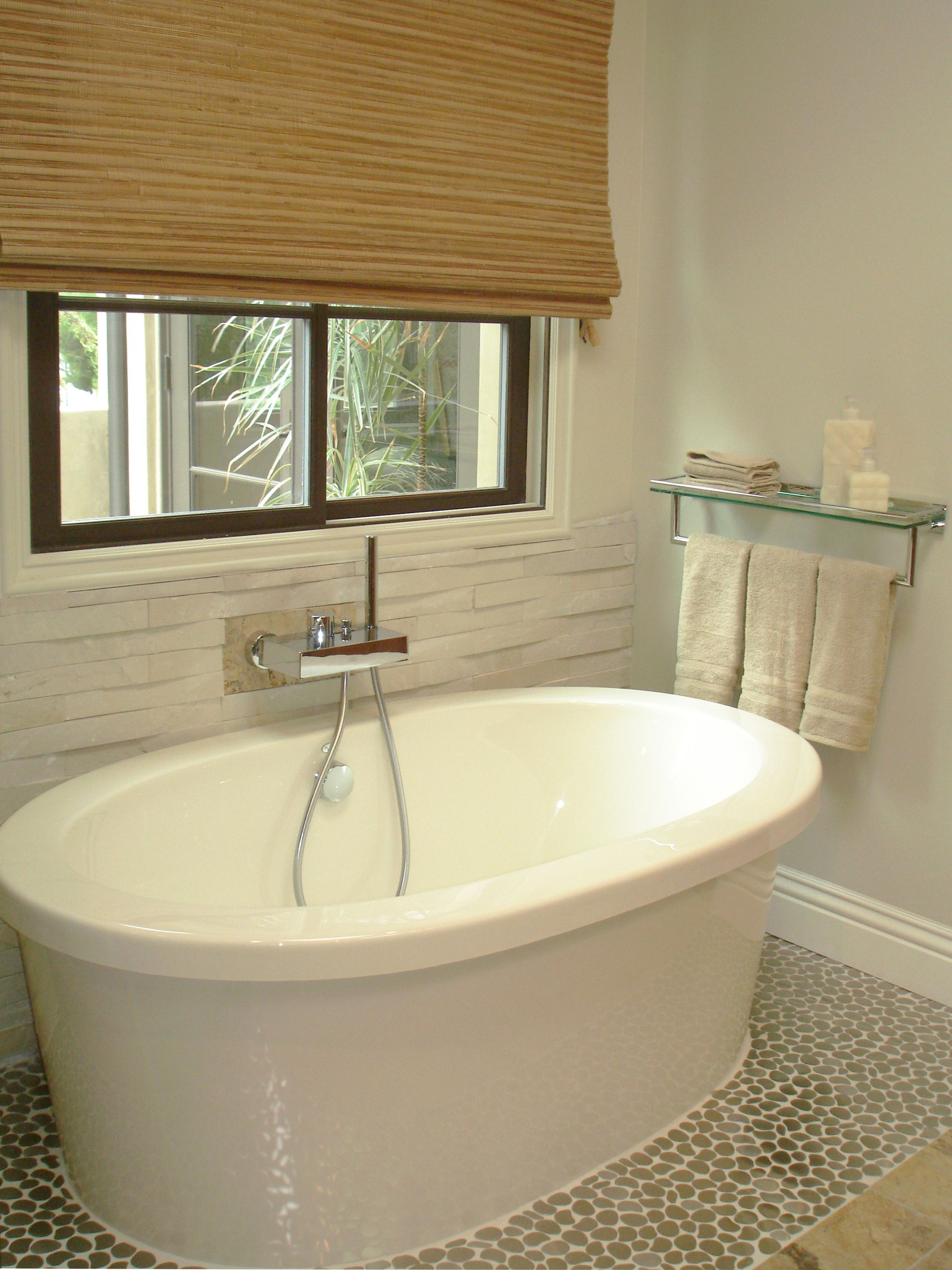 Freestanding custom tub surrounded by natural stacked stone wall ...