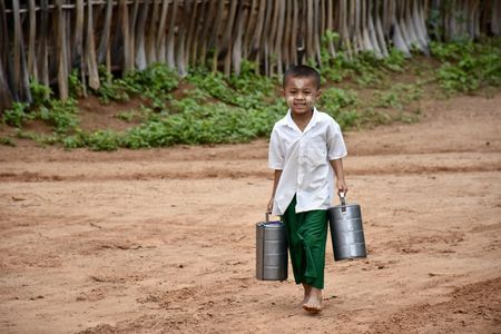 School boy bringing food to the monks Photo by Aline Jaquet — National Geographic Your Shot