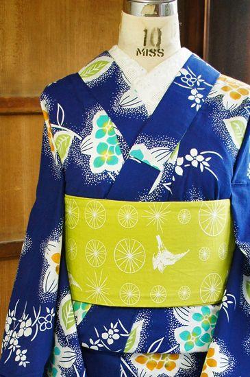 ほのかにスモークがかった紺色に近い青色の地に、空色と山吹色、黄緑色などの色選びも愛らしく、可憐な紫陽花の花枝模様が染め出された注染レトロ浴衣です。