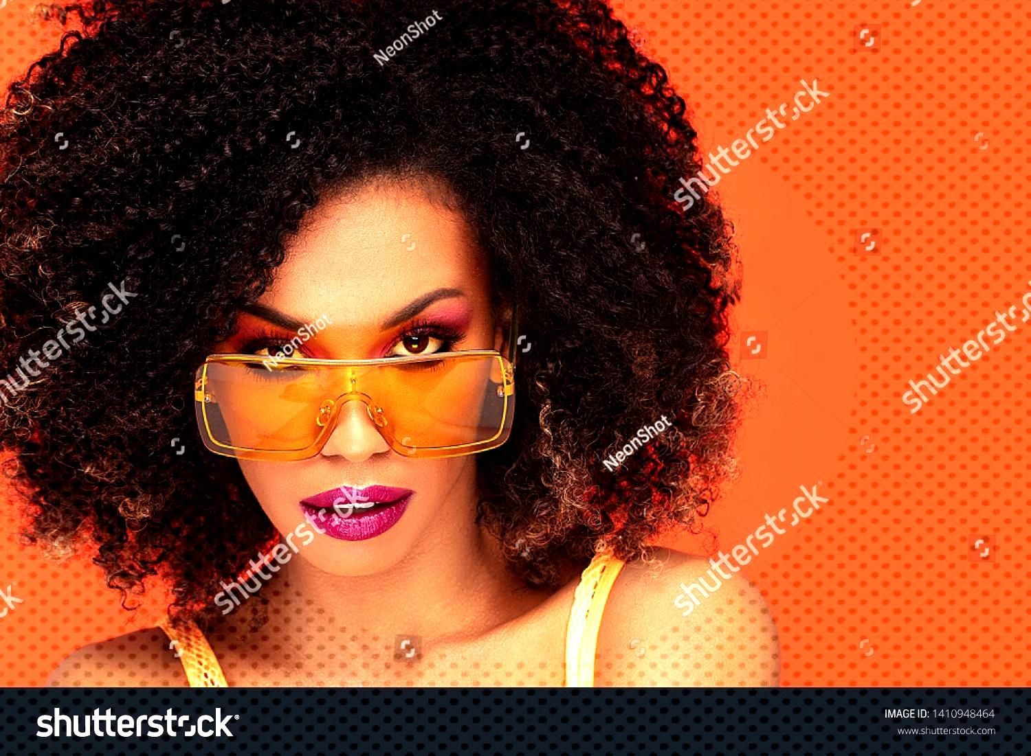 Beautiful young african american woman with afro hairstyle and glamour makeup posing in studio, loo