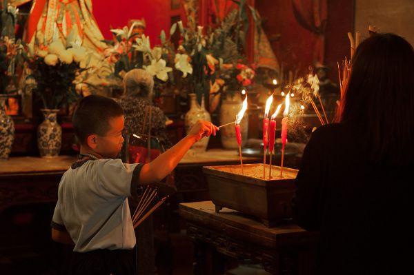 A local boy lighting a candle at Man Mo Temple, Sheung Wan, HK