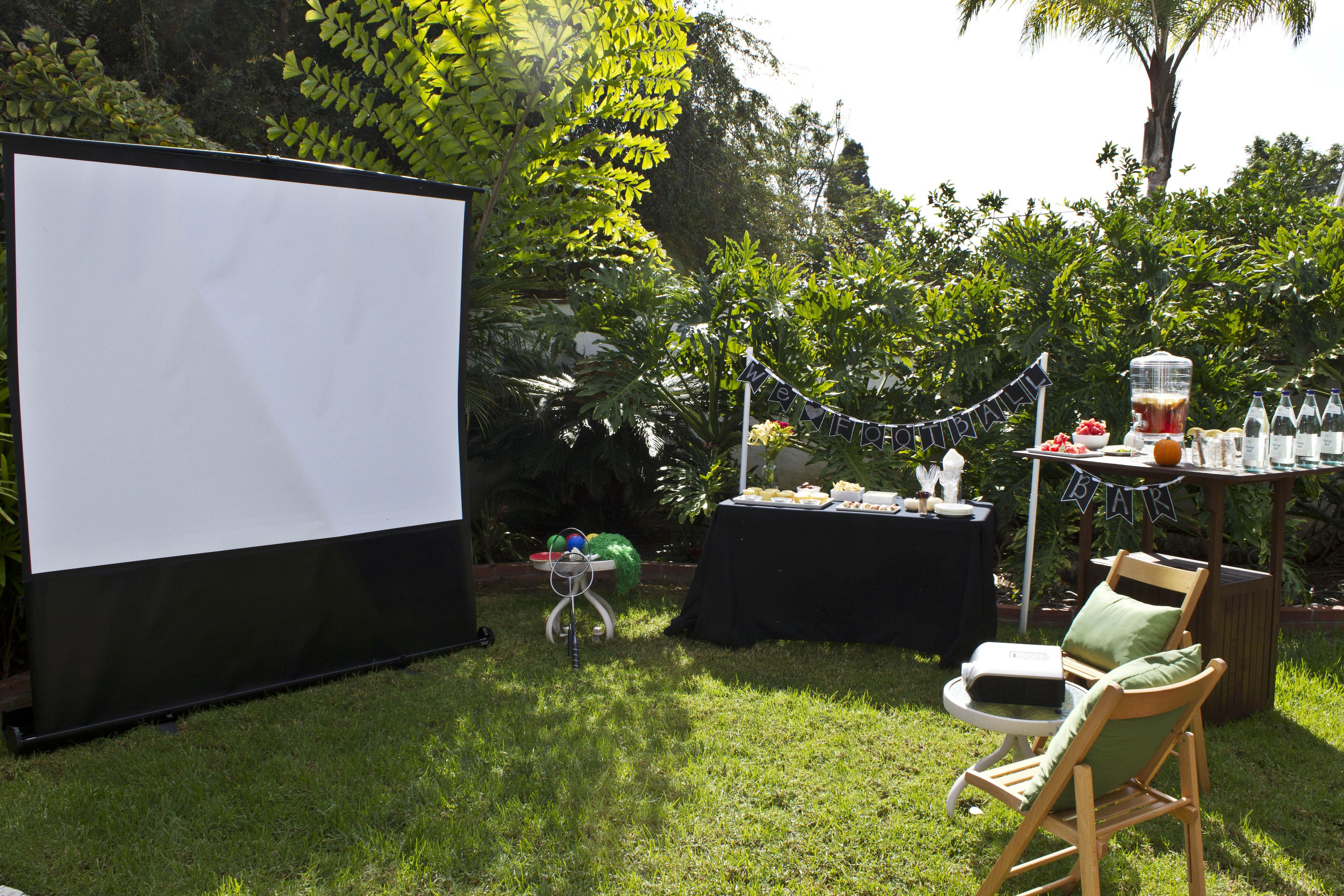 backyard football tailgating party with a projector and big screen to