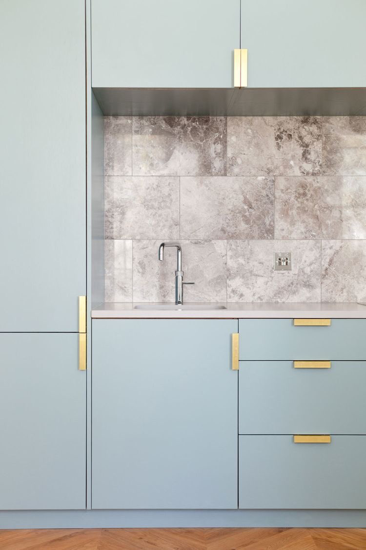 MCM light blue kitchen cabinets, gold hardware and marble back ...
