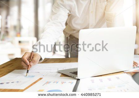 Close up of hand of business man working document and laptop in office morning light. Copyspace and concept idea of business.