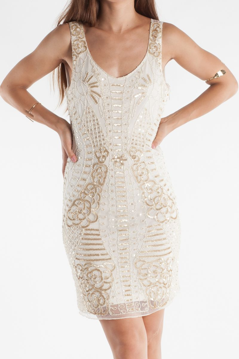 Αμάνικο φόρεμα με κεντητές χάντρες σε όλο το μήκος του. Μάκρος περίπου πάνω από το γόνατο με φερμουάρ στο πλάι και ανοιχτή πλάτη με λεπτομέρειες από διαφάνεια.
